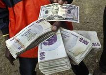 <p>Спекулянт показывает купюры доллара США и зимбабвийских долларов в Хараре 23 июня 2007 года. Уровень инфляции в Зимбабве достиг нового рекордного уровня и составил в ноябре 2007 года 26.470,8 процента в годовом исчислении. (REUTERS/Philimon Bulawayo)</p>