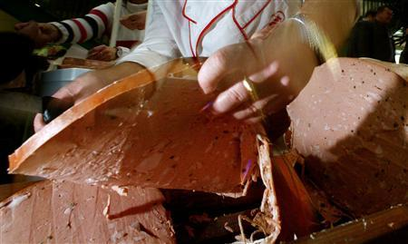A Bulgarian cook cuts slices from a large Mortadela salami in central Sofia, December 20, 2004. REUTERS/Stoyan Nenov