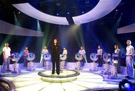 Carol Cheng (C), presenter of the Hong Kong version of the quiz show ''The Weakest Link'' stands with contestants before filming in Hong Kong August 18, 2001. REUTERS/Kin Cheung
