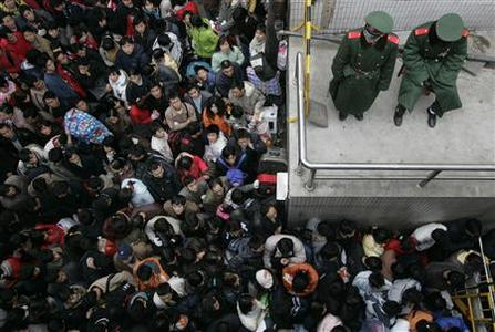 Train passengers wait outside a railway station in China's southern city of Guangzhou February 1, 2008. REUTERS/Bobby Yip