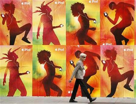 A woman walks past a billboard in downtown San Francisco, July 10, 2007. Portable media players such as iPods are unlikely to interfere with heart pacemakers, a Food and Drug Administration researcher reported on Thursday. REUTERS/Mike Blake