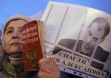 <p>Женщина держит копию конституции РФ и портрет Василия Алексаняна на митинге в Москве, 1 февраля 2008 года. Районный суд в Москве отклонил просьбу о переводе в больницу бывшего вице-президента ЮКОСа Василия Алексаняна, который говорит, что умирает от СПИДа и лишен в тюрьме медицинской помощи. REUTERS/Denis Sinyakov (RUSSIA)</p>