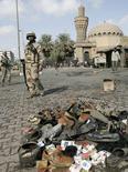 """<p>Иракский солдат стоит вблизи собранных вещей погибших при взрывах смертниц в Багдаде, 1 февраля 2008 года. По меньшей мере 72 человека погибли и около 150 получили ранения в результате взрывов бомб на многолюдных """"птичьих рынках"""" в Багдаде в пятницу, сообщила полиция. REUTERS/Mahmoud Raouf Mahmoud (IRAQ)</p>"""