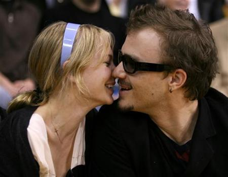 Heath Ledger (R) kisses Michelle Williams during the NBA game between the San Antonio Spurs and the Los Angeles Lakers in Los Angeles March 6, 2006. In her first statement since the death of her former companion Heath Ledger, Williams asked for privacy for her and daughter Matilda and said she suffers from a broken heart. REUTERS/Lucy Nicholson
