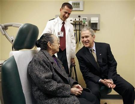 President George W. Bush talks with a patient as he tours the OneWorld Community Health Center in Omaha, Nebraska, December 5, 2007. Health experts denounced Bush's 2009 federal budget request on Monday, calling it a disaster for the health of Americans and saying they would look to Congress to change it. REUTERS/Kevin Lamarque