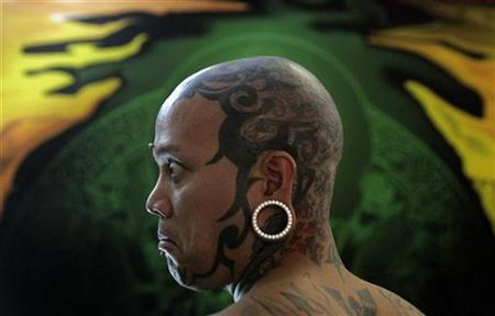 Tattoos are seen on the head of a man at the International London Tattoo Convention, October 5, 2007. Facial piercings and tattoos may be becoming more common and prominent -- but that doesn't mean they are any more accepted in the workplace, according to a new study. REUTERS/Alessia Pierdomenico