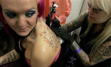 A woman has her back tattooed at the International London Tattoo Convention, October 5, 2007. The tattoo of the future may be good for your health rather than just your image. REUTERS/Alessia Pierdomenico