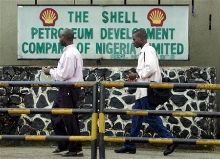 People walk past the Dutch oil giant Shell's sign board in Port Harcourt in the volatile Niger delta region of Nigeria September 23, 2005. REUTERS/George Esiri