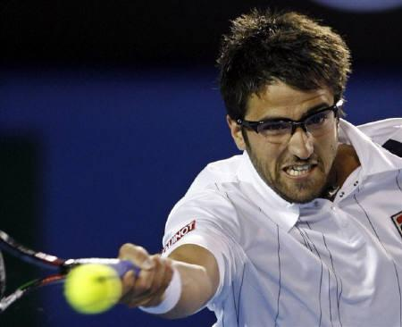Serbia's Janko Tipsarevic hits a shot to Switzerland's Roger Federer at the Australian Open tennis tournament in Melbourne in this January 19, 2008 file photo. Tipsarevic is out of the Davis Cup World Group first-round tie with Russia in Moscow because of a stomach bug. REUTERS/Petar Kujundzic