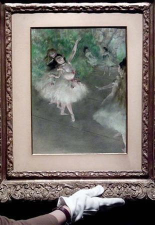 Edgar Degas' painting ''Ballet Dancer'' is put in place by a Sotheby's porter in a gallery at auctioneers Sotheby's in London, April 16, 2002. Tucked away beside a dry cleaners in a dark Paris courtyard, the firm that supplied Impressionist master Degas with the brilliant pastel colors used in some of his most famous pictures is still in business. REUTERS/Ian Waldie