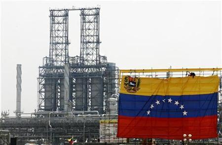 Oil workers hang a Venezuelan flag at the Jose Complex during celebrations in Barcelona, Venezuela, May 1, 2007, Exxon Mobil Corp has moved to freeze up to $12 billion in Venezuelan assets around the world as the U.S. company fights for payment in return for the state's takeover of a huge oil project last year. REUTERS/Jorge Silva