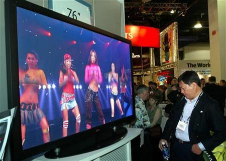 Kazuaki Kawamura of San Diego looks over the world's first 76-inch plasma television at the LG Electronics booth during the Consumer Electronics Show in Las Vegas, Nevada, January 8, 2004. REUTERS/Steve Marcus/Las Vegas Sun