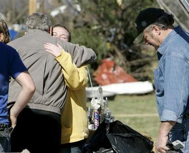 President Bush hugs Amber Warner, 14, during a walk through a tornado-damaged neighborhood with state and local officials in Lafayette, Tennessee February 8, 2008. REUTERS/Larry Downing