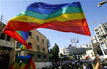 Participants wave flags and balloons during a Gay Parade in Jerusalem June 21, 2007. Israel's attorney general said on Sunday that same sex-couples will be allowed to adopt children that are not biologically linked to either partner. REUTERS/Ronen Zvulun