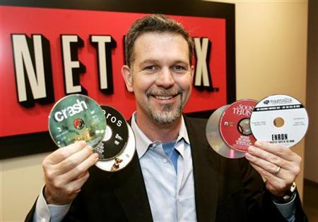 Reed Hastings, CEO of Netflix Inc., a online DVD-rental service, holds several DVD's as he poses at the Netflix offices in Beverly Hills, California December 8, 2005. Online video rental company Netflix Inc said on Monday it would exclusively stock Blu-ray high-definition DVDs after a decision by some the world's biggest movie studios in favor of the Sony Corp developed format. REUTERS/Fred Prouser