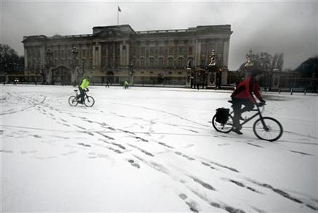 Commuters brave the snow as they cycle outside Buckingham Palace in London February 8, 2007. London will adopt a bicycle hire scheme similar to a popular initiative in Paris under a $1 billion (513 million pound) cycling investment package announced by the mayor on Monday. REUTERS/Dylan Martinez