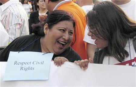 Unidentified marchers laugh during an immigration rally in Los Angeles May 17, 2007. Non-Hispanic whites will become a minority in the United States by 2050, with immigrants and their children driving 82 percent of U.S. population growth in coming years, a new study said on Monday. REUTERS/Staff