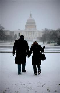 A couple walk through snow as they take in the sights of the Capitol Building during the first snow of the 2007 winter season on the Washington Mall January 21, 2007. Love really is blind, at least when it comes to looking at others, U.S. researchers reported on Tuesday. REUTERS/Jason Reed