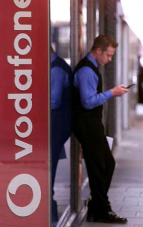 A man uses a mobile phone next to a Vodafone sign in a file photo. REUTERS/File