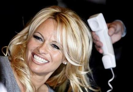 Actress Pamela Anderson smiles as she talks on the phone with France's Actress Brigitte Bardot (not pictured) during a visit to Bardot's foundation for animals rights in Paris February 14, 2008. REUTERS/Charles Platiau