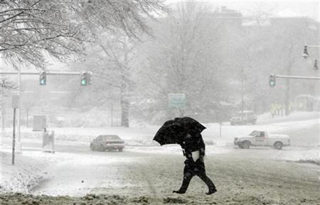 A pedestrian crosses a snow covered street during a winter snow storm in Boston, Massachusetts January 14, 2008. Genes that helped early humans adapt to cold climates may be driving metabolism-related diseases such as obesity or diabetes in many countries, U.S. researchers said on Thursday. REUTERS/Brian Snyder