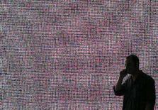 <p>Un uomo al cellulare davanti a un grande schermo. REUTERS/Hannibal Hanschke (GERMANY)</p>