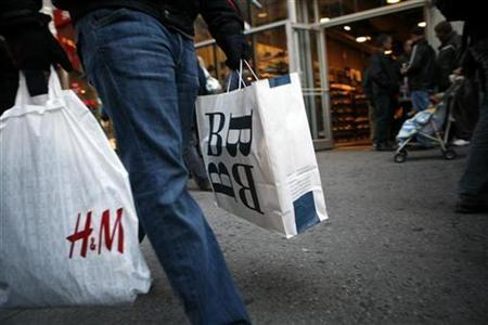 A shopper carrying shopping bags walks past retail stores in New York's Times Square November 23, 2007. Consumer sentiment fell sharply in early February to levels associated with previous recessions, a survey showed on Friday. REUTERS/Brendan McDermid