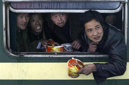 Passengers ask for water for their instant noodles inside a train stranded at a railway station due to snowfall in Nanjing, in Jiangsu province, January 28, 2008. REUTERS/Sean Yong