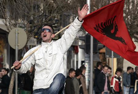 A Kosovo Albanian man waves an Albanian flag in celebration for up-coming province's independence in the ethnically divided town of Mitrovica February 15, 2008. Serbia swore in President Boris Tadic on Friday two days before Kosovo proclaims independence, in the country's most traumatic moment since it was bombed by NATO in 1999 to end ethnic cleansing in the province. REUTERS/Hazir Reka