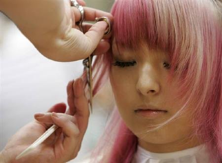 A stylist cuts a model's hair in Tokyo in this July 10, 2007 file photo. REUTERS/Michael Caronna
