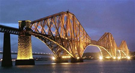 The Forth Rail Bridge is illuminated in this file picture. Opened in 1890, the bridge was the largest manmade construction of its time, as well as being the first bridge to be constructed of steel, and took seven years to build at a cost of 3 million pounds. REUTERS/Stringer