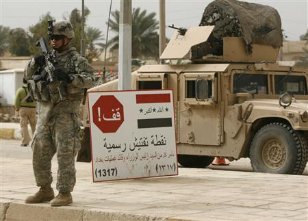 A U.S. soldier stands guard near a sign that reads ''Stop; an official checkpoint authorized by the Iraqi prime minister and Baghdad's operations chief'' on a road during a patrol in Salman Pak, about 45 km (25 miles) south of Baghdad, February 18, 2008. REUTERS/Mahmoud Raouf Mahmoud