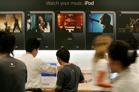A customer (2nd L) discusses an Apple product with a shop assistant (C) while customers shop at an Apple store in Tokyo in this August 25, 2006 file photo. REUTERS/Kiyoshi Ota/Files