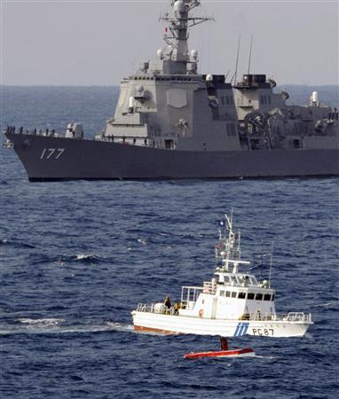 Japan Maritime Self-Defense Force's Atago (top), equipped with high-tech Aegis radar systems, is seen behind a Japanese Coast Guard vessel and the floating wreckage of the fishing boat which collided with the naval destroyer in the Pacific Ocean off the coast of Chiba Prefecture, east of Tokyo, February 19, 2008. REUTERS/Kyodo