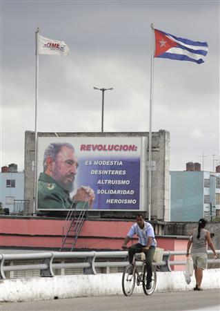 People pass a billboard showing Cuba's retired leader Fidel Castro in Havana, February 19, 2008. REUTERS/Enrique De La Osa
