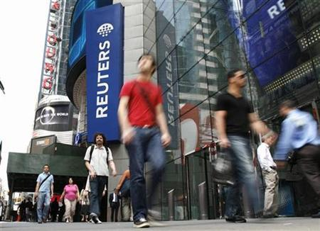 Pedestrians walk past the Reuters building in Times Square in New York, May 15, 2007. Thomson won conditional approval from the European Commission and the U.S. Department of Justice to buy Reuters, a deal that will create the world's leading provider of news and data for professional markets. REUTERS/Gary Hershorn