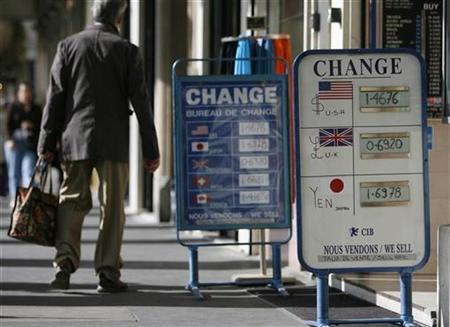 A man walks past signs outside a currency exchange bureau in Paris September 24, 2007. The U.S. dollar could get some relief versus the euro and Swiss franc in the months ahead as European banks, with balance sheets besieged by the credit crisis, take advantage of a steeper Treasury yield curve to improve earnings and rebuild their balance sheets. REUTERS/Vincent Kessler