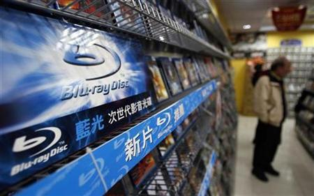 A man stands beside a rack of Blu-ray disc movies inside a DVD rental shop in Taipei February 18, 2008. General Electric Co's Universal Pictures, one of a few studios using the Toshiba Corp-backed HD DVD format, said on Tuesday it will switch to the rival Blu-ray format now that Toshiba has officially pulled the plug on HD DVD. REUTERS/Nicky Loh
