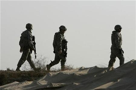 U.S. soldiers patrol at their new outpost, Carver, that is being built in Salman Pak, south of Baghdad, February 16, 2008. The U.S. military has been stretched dangerously thin by the Iraq war, according to almost 90 percent of retired and current military officers polled on the state of America's armed forces. REUTERS/Mahmoud Raouf Mahmoud