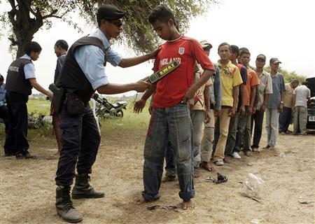 Police check bus passengers at a checkpoint in Tositolu on the outskirts of Dili February 17, 2008. REUTERS/Beawiharta