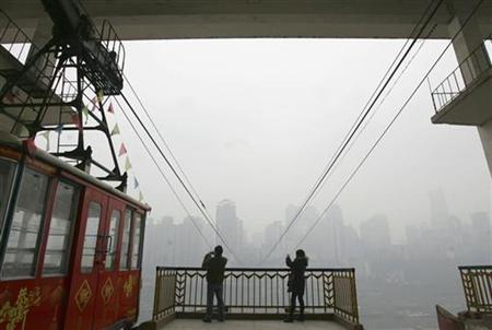 Visitors take photos of a cable car at its terminal in Chongqing municipality February 20, 2008. REUTERS/Stringer