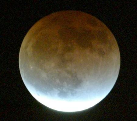 The moon is seen over London, during a lunar eclipse, May 4, 2004. REUTERS/Matt Dunham