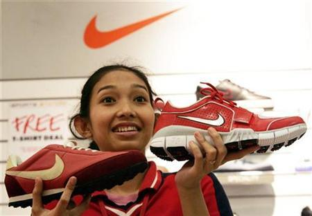 An Indonesian worker shows Nike shoes to a customer at a shopping mall in Jakarta July 17, 2007. A growing number of young Chinese consumers are buying sportswear from home-grown brands, such as Li Ning and Anta, although they still lag Nike and Adidas. REUTERS/Dadang Tri