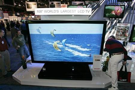 Attendees look at a 108-inch LCD television during the 2007 International Consumer Electronics Show (CES) in Las Vegas, Nevada January 8, 2007. Demand for flat panel televisions is expected to more than double to 180 million units by 2012, driven by strong sales in China and the United States, a Japanese industry group said. REUTERS/Steve Marcus