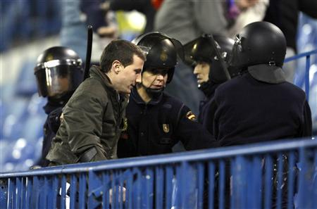 Spanish riot police surround a supporter during Atletico Madrid's UEFA Cup third round football match against Bolton Wanderers at Vicente Calderon stadium in Madrid February 21, 2008. Bolton Wanderers have made an official protest to UEFA about the treatment of their fans by Spanish police during Thursday's UEFA Cup tie against Atletico Madrid. REUTERS/Andrea Comas