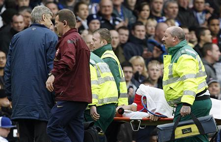 Arsenal's manager Arsene Wenger (L) watches as his team's player Eduardo is carried off during their Premier League football match against Birmingham City at St. Andrews in Birmingham, February 23, 2008. REUTERS/Darren Staples NO ONLINE/INTERNET USAGE WITHOUT A LICENCE FROM THE FOOTBALL DATA CO LTD. FOR LICENCE ENQUIRIES PLEASE TELEPHONE ++44 (0) 207 864 9000..