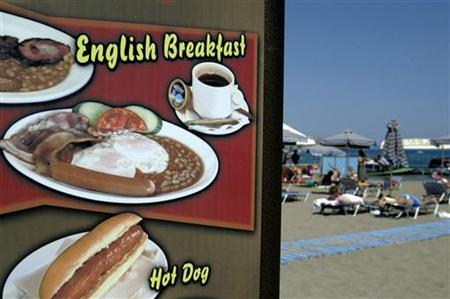 A sign informing tourists that British breakfast is offered at a beach bar of Faliraki resort on the Dodecanese island of Rhodes August 24, 2003. Some 1,000 Chinese cooks are coming to England to learn how to make bubble and squeak, bangers and mash and other English delicacies for athletes and tourists at the Olympics in China this summer. REUTERS/Yiorgos Karahalis
