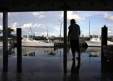 A worker awaits the arrival of boats carrying stone crabs at a factory in the Florida Keys, October 18, 2006. Thousands of small businesses across the United States rely on foreign, seasonal workers to shuck oysters, mow lawns, clean hotel rooms and pick crops. REUTERS/Carlos Barria