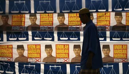 A Malaysian Muslim man walks to the mosque for his afternoon prayer past election campaign posters of Prime Minister Abdullah Ahmad Badawi's party in the village of Sabak, in the opposition stronghold state of Kelantan, February 25, 2008. The Internet is changing the face of Malaysian politics, becoming a virtual political party of its own as the country gears up for elections next month. REUTERS/Bazuki Muhammad