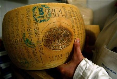 An Italian grocer shows off his Parmesan cheese inside a shop in central Rome May 20, 2003. Germany will not have to remove the name ''Parmesan'' from cheeses on sale that are not made in Italy's Parma region, Europe's highest court said on Tuesday. REUTERS/Alessia Pierdomenico